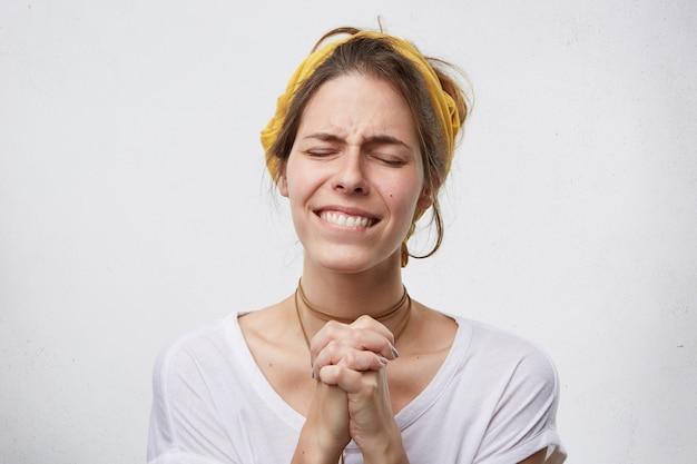 Emotionale frau, die ihre augen schließt und die lippen krümmt, die weinen und die handflächen zusammenhalten, mit einigen problemen, die um glück betteln. niedergeschlagene frau, die mit hoffnung auf besseres betet