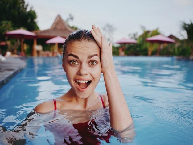 Emotionale frau im roten badeanzug in der poolferien-luxushotelinsel