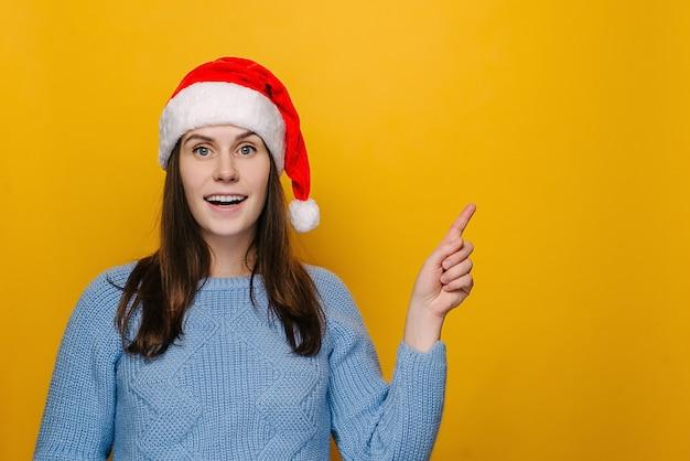 Emotionale frau in weihnachtsmütze, zeigt mit dem vorderfinger auf die leerstelle, lächelt glücklich, zeigt werbung, trägt winterpullover, isoliert über gelber wand. frohe neujahrsfeier frohe feiertage