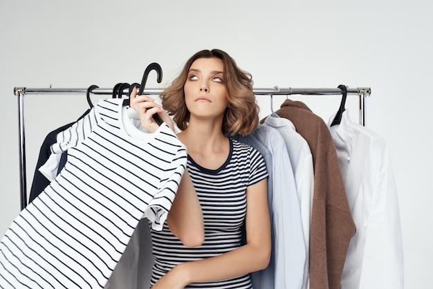 Emotionale frau kleiderbügel kommode mode innen heller hintergrund. foto in hoher qualität