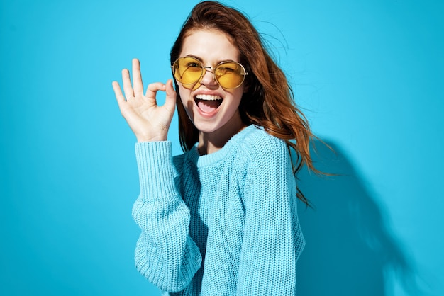 Emotionale frau mit brille und blauem pullover-lebensstil lässig tragen blauen hintergrund.