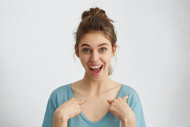 Emotionale frau mit hochgezogenem haar, blauen augen und weißen zähnen, die froh ist, dass sie zur anführerin gewählt wurde. überraschte schöne freudige frau mit hellem haar, das auf sich selbst zeigt.