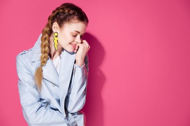 Emotionale frau mit zöpfen dekoration modische kleidung posiert rosa hintergrund