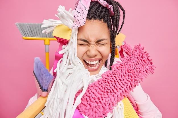 Emotionale frau schreit laut und verwendet verschiedene reinigungswerkzeuge