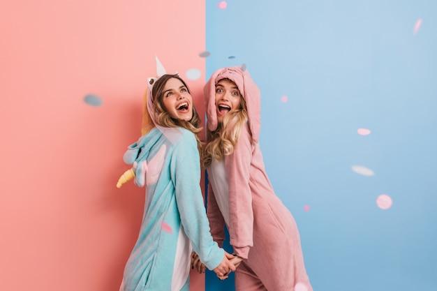 Emotionale frau trägt rosa kigurumi, der nach vorne lacht