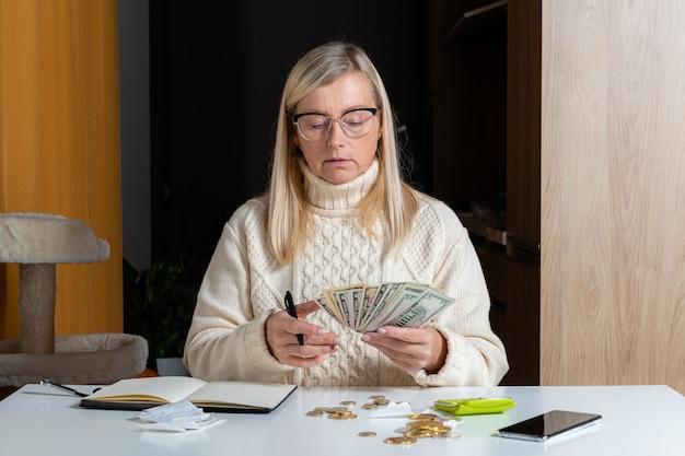 Emotionale freiberufliche frau, die budget im heimbüro, ausgabeneinnahmen und -ausgaben berechnet, arbeit vom hauptkonzept