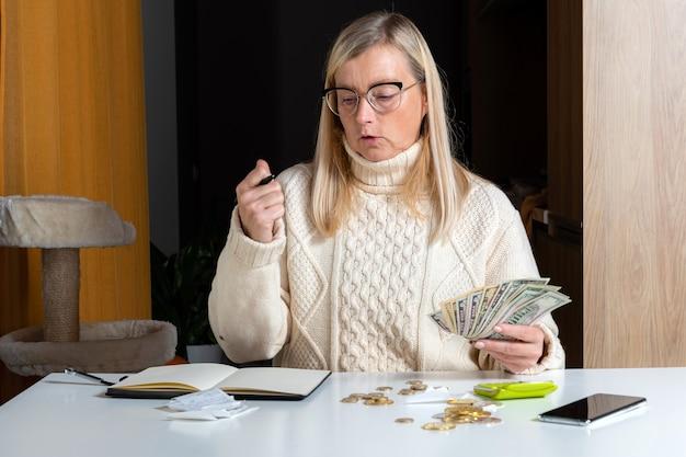 Emotionale freiberufliche frau, die budget im home office, ausgabeneinnahmen und ausgaben berechnet