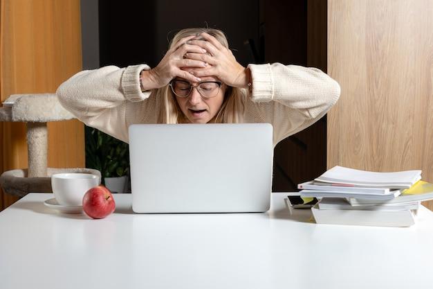 Emotionale freiberufliche frau, die im heimbüro arbeitet, überrascht starrt auf laptop-bildschirm schockiert durch e-mail erhalten, arbeit von zu hause konzept