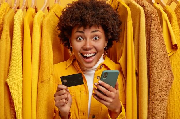 Emotionale fröhliche einkaufsfrau benutzt handy, um online zu bezahlen, hält kreditkarte, steht zwischen gelben pullovern auf kleiderbügeln