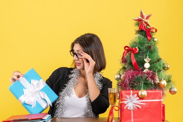 Emotionale geschäftsdame im anzug mit brille, die ihr geschenk betrachtet und an einem tisch mit einem weihnachtsbaum darauf im büro sitzt