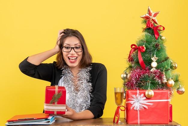Emotionale glückliche geschäftsdame im anzug mit brille, die ihr geschenk zeigt und an einem tisch mit einem weihnachtsbaum darauf im büro sitzt