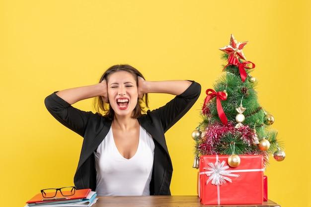 Emotionale glückliche junge frau, die ihre ohren schließt, die an einem tisch nahe geschmücktem weihnachtsbaum im büro auf gelb sitzen