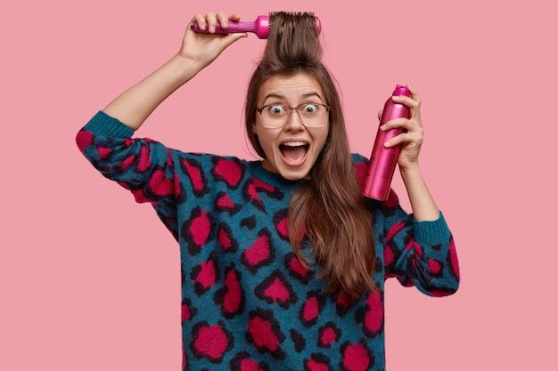 Emotionale glückliche junge frau kämmt fransen, verwendet haarspray für die herstellung einer schönen frisur, überrascht, einladung auf party zu erhalten, bereitet