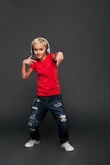 Emotionale hörende musik des kindes des kleinen jungen mit dem kopfhörertanzen.