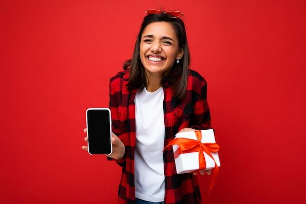 Emotionale hübsche glückliche junge brünette frau isoliert auf roter hintergrundwand mit weißem casual