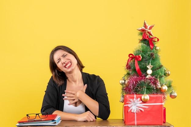 Emotionale junge frau, die an einem tisch nahe geschmücktem weihnachtsbaum im büro auf gelb sitzt
