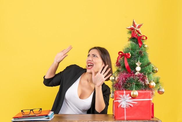 Emotionale junge frau, die etwas betrachtet, das an einem tisch nahe dekoriertem weihnachtsbaum im büro auf gelb sitzt
