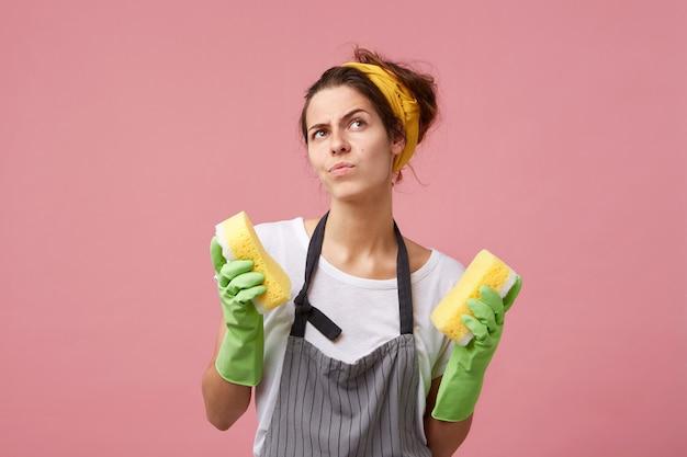 Emotionale junge frau, die schürze und gummihandschuhe trägt, die von sauberkeit besessen sind und schwämme in beiden armen halten, während sie in der küche aufräumen. hygiene-, hausarbeits- und reinigungskonzept