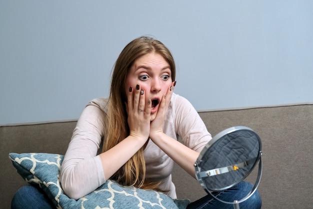 Emotionale junge frau, die sich den schminkspiegel ansieht, während sie zu hause auf dem bett sitzt, mädchen öffnete überrascht den mund, hält das gesicht mit den händen