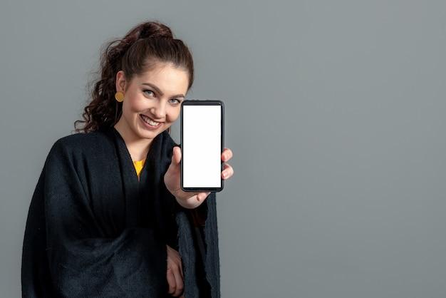 Emotionale junge frau, die smartphone mit leerem touchscreen mit kopienraum zeigt, lokalisiert auf grauem hintergrund