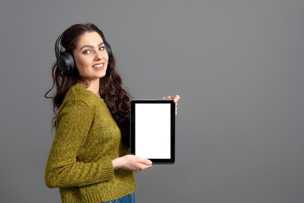 Emotionale junge frau, die tablet-computer mit leerem touchscreen mit kopienraum zeigt, lokalisiert auf grauer wand