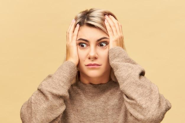 Emotionale junge frau im übergroßen kuscheligen pullover, der hände auf ihrem kopf hält und in panik und schock ist und vergesslichen blick hat. frustriertes nervöses mädchen, das ausflippt und sich sorgen macht, weil sie es vermasselt hat