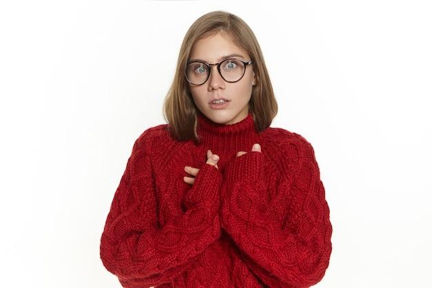 Emotionale junge frau mit käferaugen, die einen langärmeligen strickpullover und eine brille trägt, die einen überraschten blick hat, den mund öffnet und unerwartete neuigkeiten erhält. menschliche mimik, emotionen und gefühle