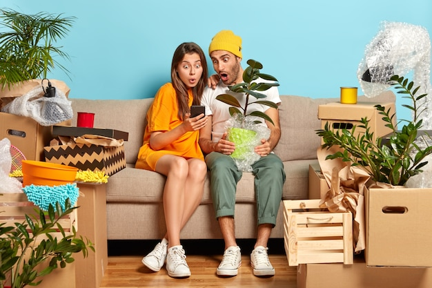 Emotionale junge frau und mann starren auf smartphone-gerät, suchen neues design für wohnzimmer, ziehen in neuen wohnsitz um, halten topfpflanze, echtes durcheinander mit kartons herum. junge hausbesitzer auf dem sofa