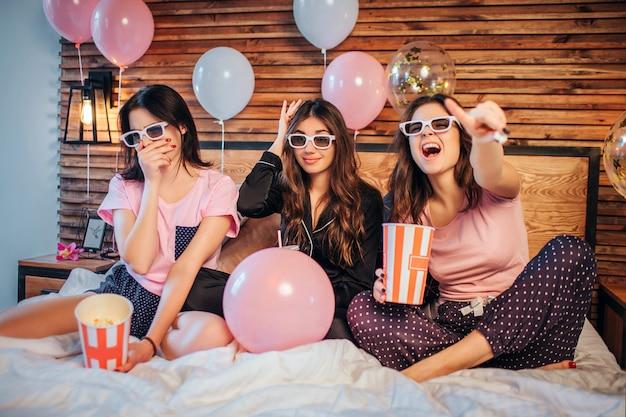 Emotionale junge frauen sitzen auf dem bett im festlichen raum. sie schauen sich filme durch spezielle brillen an. frauen tragen pyjamas. sie haben party.