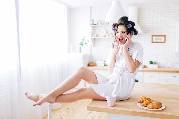 Emotionale junge sorglose frau sitzen auf tisch und sprechen am telefon. erstaunte haushälterin in der küche. tragen eines weißen morgenmantels. leben ohne arbeit. stilvolle frau mit lockenwicklern im haar.