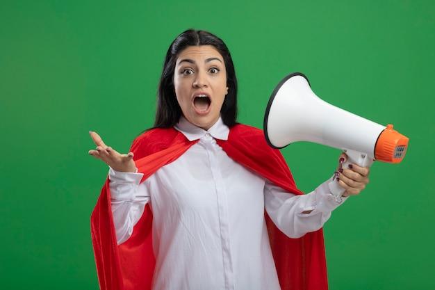 Emotionale junge superfrau hält lautsprecher an ihren mund und überrascht isoliert auf grüner wand