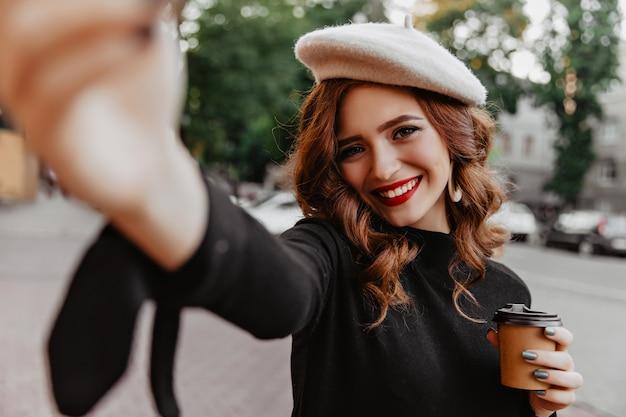Emotionale kaukasische frau, die selfie macht, während tee im herbst trinkt. frohes ingwermädchen trägt baskenmütze, die oktobertag genießt.
