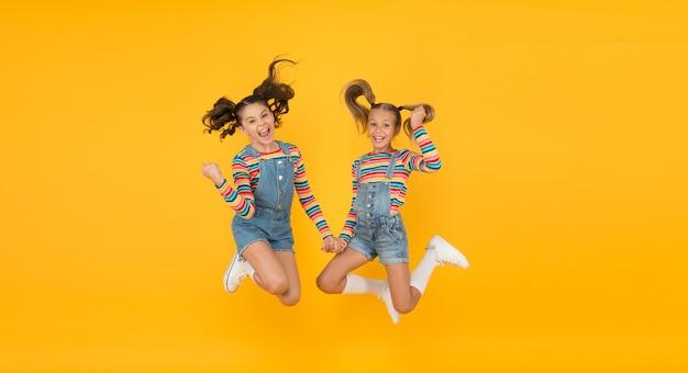 Emotionale kinder. mode-geschäft. muss zubehör haben. moderne mode. kindermode. kleine mädchen, die regenbogenkleidung tragen. glück. mädchen langes haar. nette kinder gleichen outfits. trendig und schick.