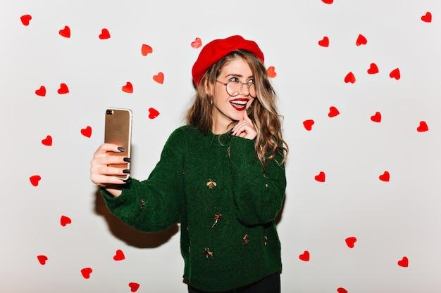 Emotionale kulrige frau in der baskenmütze, die telefon für selfie auf weißer wand verwendet