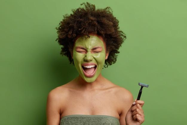 Emotionale lockige junge frau, eingewickelt in weiches badetuch hält rasiermesser, das enthaarung haben wird, wendet schönheitsmaske für hautbehandlung an, hält mund weit offen isoliert über grüner wand