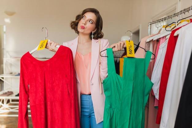 Emotionale lustige attraktive frau, die bunte kleider auf kleiderbügel im bekleidungsgeschäft hält