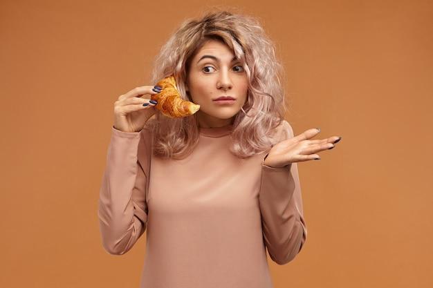 Emotionale lustige überraschte junge frau mit rosafarbenem haar, das erstaunen ausdrückt, das augen weit öffnet, hilflos gestikuliert, während des telefongesprächs ratlos ist