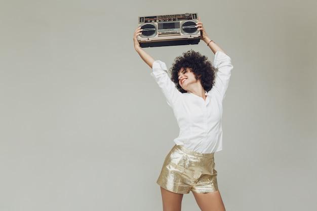 Emotionale retro-frau gekleidet im hemd, das boombox hält.