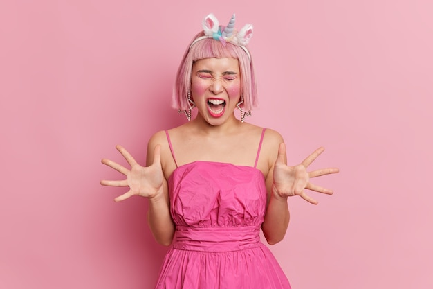 Emotionale rosahaarige asiatin mit make-up und strasssteinen im gesicht hebt handflächen schreit wütend, irritiert von etwas, trägt ein stilvolles einhorn-stirnband