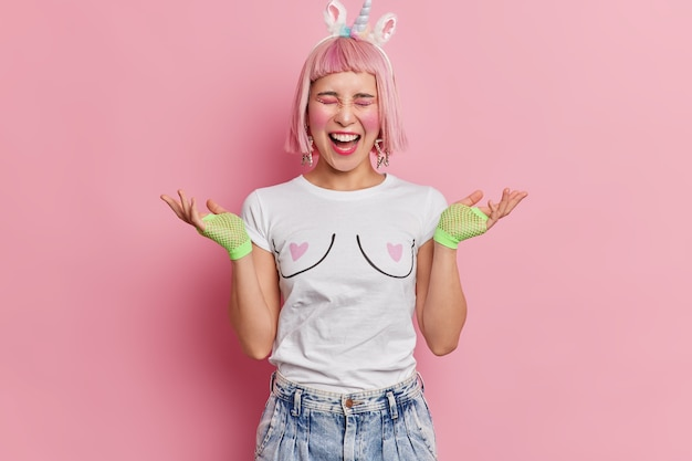 Emotionale rosahaarige junge asiatin breitet palmen aus und ruft laut in lässigem t-shirt gekleidet und jeans hat helles make-up