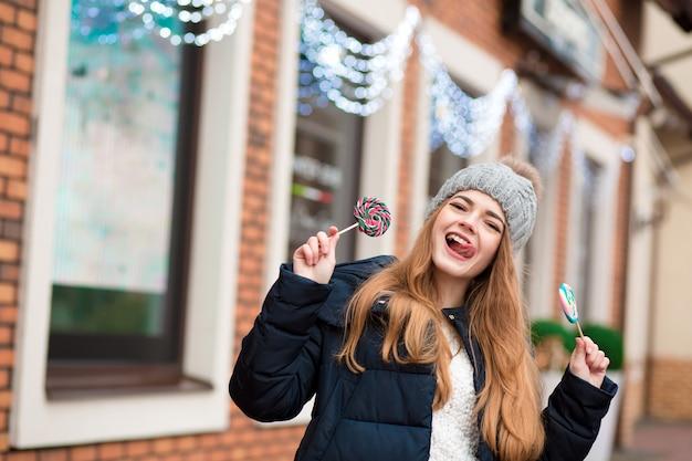 Emotionale rothaarige junge frau, die graue strickmütze trägt und bunte weihnachtsbonbons in der nähe des schaufensters hält