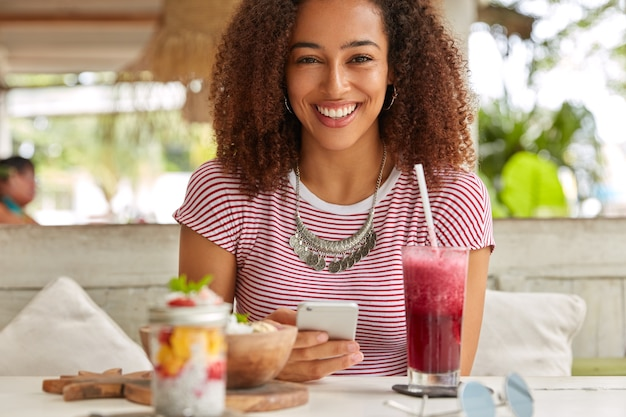 Emotionale schwarze junge frau mit knackigem haar, zahnigem lächeln, hält modernes handy, nutzt kostenloses wlan in der cafeteria zum networking, trinkt frischen fruchtsmoothie, trägt lässiges t-shirt, hat freizeit