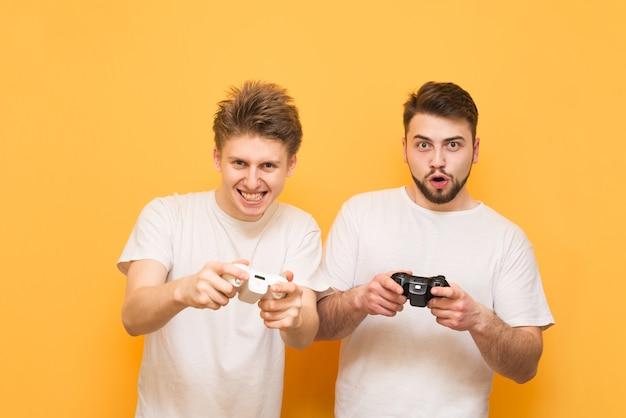 Emotionale spieler mit gamepad in der hand, die videospiele spielen, die sich auf gelb konzentrieren