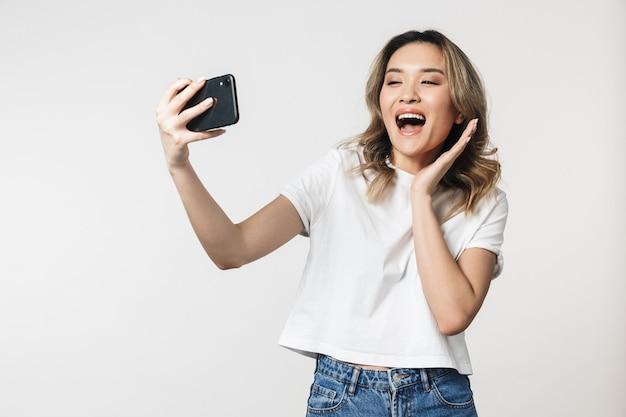 Emotionale süße junge frau, die isoliert über weißer wand posiert und mit dem handy spricht, macht ein selfie