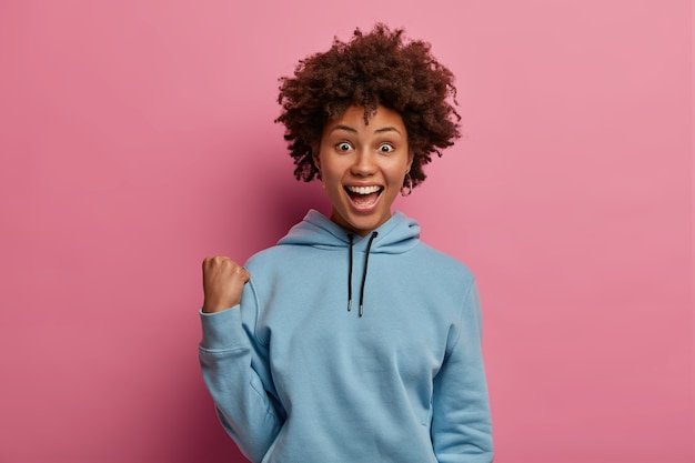 Emotionale überglückliche lockige frau hebt die geballte faust, hat eine optimistische stimmung, ruft nach der lieblingsfußballmannschaft, trägt einen lässigen blauen hoodie, bekommt exzellente neuigkeiten, reagiert auf etwas fantastisches, steht drinnen