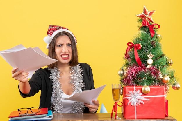 Emotionale verärgerte geschäftsdame im anzug mit weihnachtsmannhut und neujahrsdekorationen, die dokumente halten und an einem tisch mit einem weihnachtsbaum sitzen