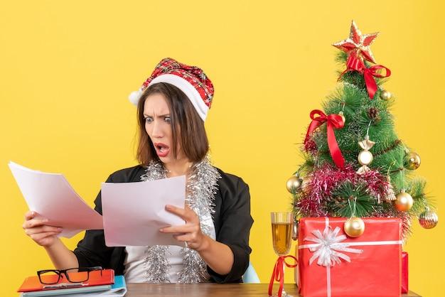 Emotionale verwirrte geschäftsdame im anzug mit weihnachtsmannhut und neujahrsdekorationen, die dokumente auf ihrem kopf betrachten und an einem tisch mit einem weihnachtsbaum darauf im büro sitzen