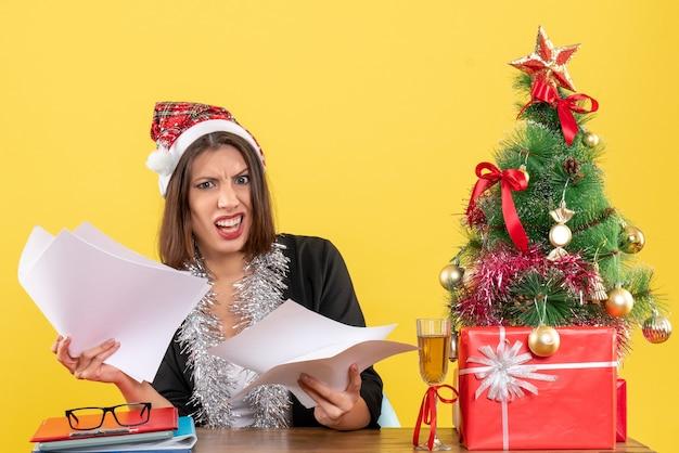 Emotionale verwirrte geschäftsdame im anzug mit weihnachtsmannhut und neujahrsdekorationen, die dokumente halten und an einem tisch mit einem weihnachtsbaum darauf im büro sitzen
