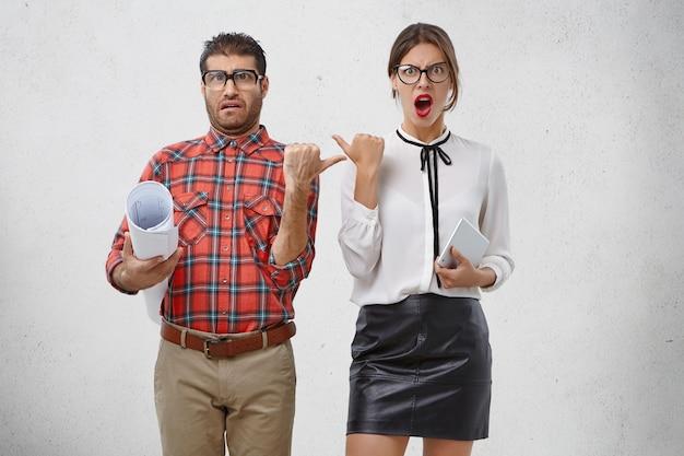 Emotionale weibliche und männliche mitarbeiter zeigen mit unzufriedenheit aufeinander,