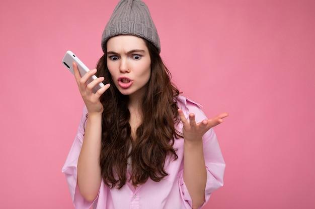 Emotionale wütende attraktive junge brünette frau mit stilvollem rosa hemd und grauem hut einzeln auf rosafarbenem hintergrund, die in der hand hält und mit dem mobiltelefon kommuniziert und sprachnachrichten aufzeichnet.